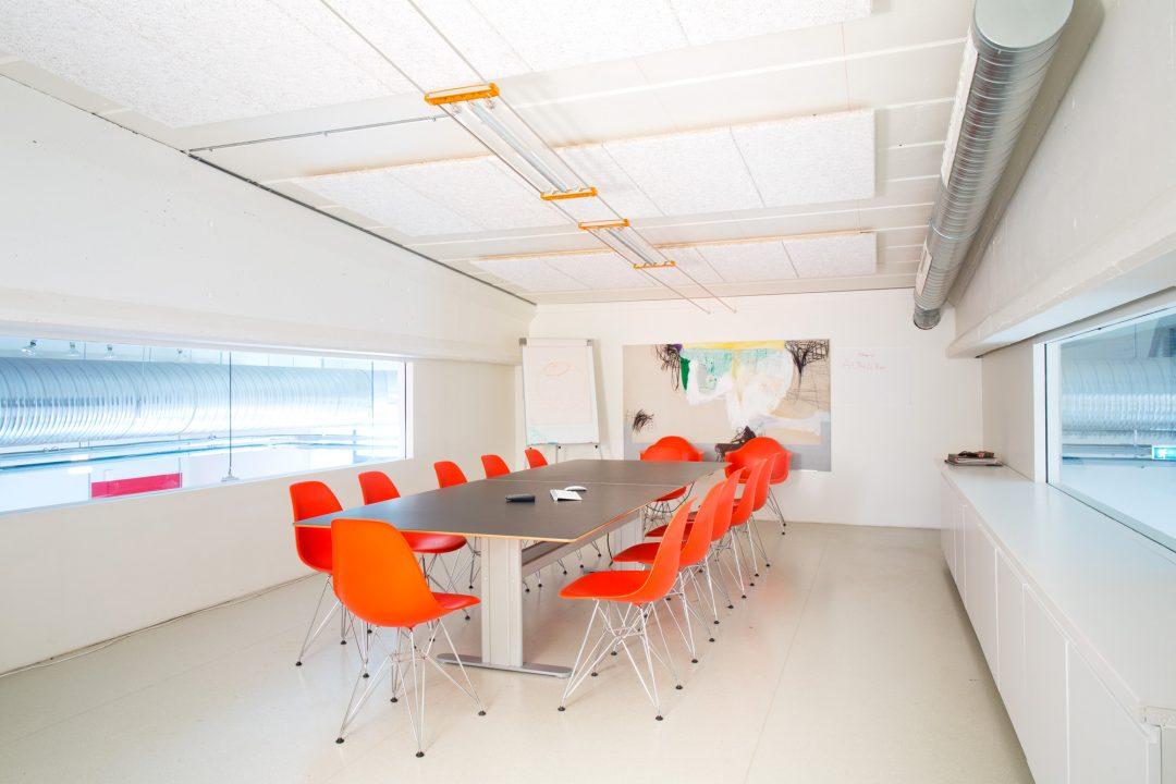 Møterom med stort bord, oransje stoler og maleri i bakgrunnen